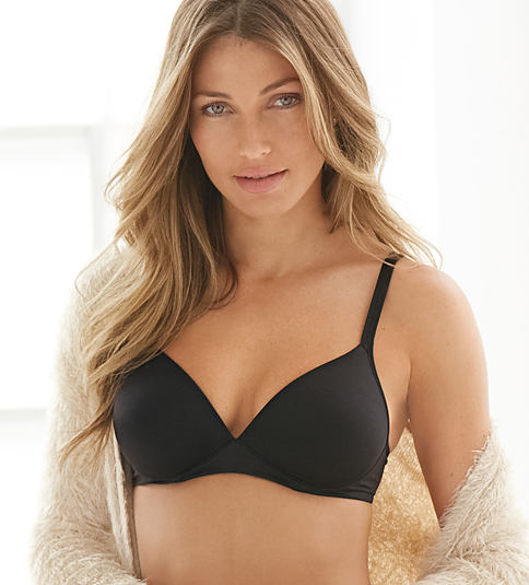 A woman wearing a black bra, putting on an off-white lace blouse. Bras. Shop now.