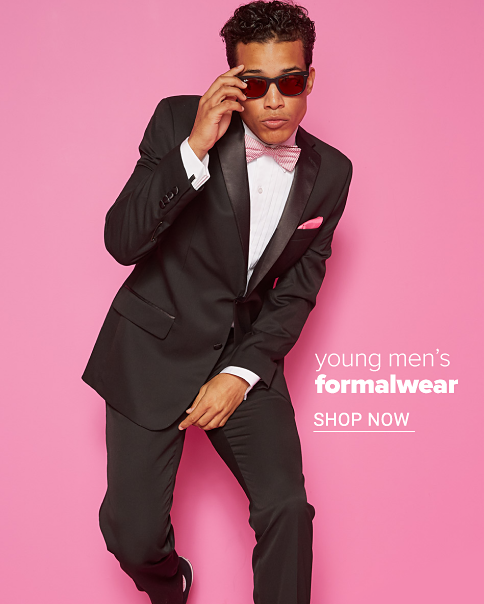 A young man in a black tuxedo, white dress shirt and pink bow tie. Young men's formalwear. Shop now.