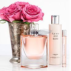 Bottles of Lancome La vie est belle beauty & fragrance products next to flowers. Shop La vie est belle.
