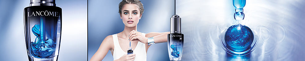A bottle of Lancome serum. A woman opening a bottle of the same serum. Another bottle of serum. A view down the top of the bottle of serum. Lancome Paris. New advanced Genifique Sensitive Serum is boosted with pure ferulic acid & vitamin E inside a soothing base of centella asiatica to instantly calm distressed skin & protect against environmental aggressors for visibly healthy-looking skin. Shop now.