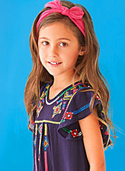 A girl wearing a navy blue dress with a multi colored print on it. Shop girls' 4-6X.