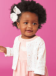 A baby girl wearing a pink dress with a white cardigan. Shop baby girls.
