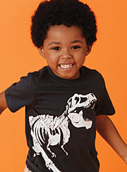 A boy wearing a black and white dinosaur graphic T-shirt. Shop toddler boys.