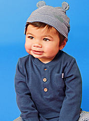 A baby boy wearing a gray bear-eared knit cap and a blue-gray henley shirt. Shop baby boys.
