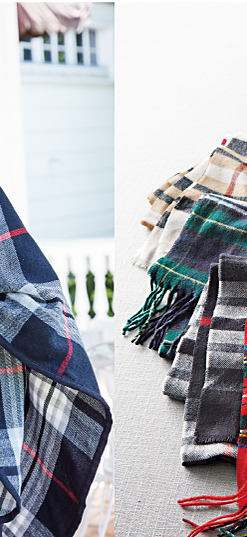 A woman wearing a red hat & a blue, white & red plaid wrap. An assortment of plaid wraps in a variety of colors. The Cozy Shop at Belk. Shop robes.