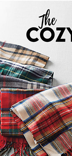 A woman wearing a red hat & a blue, white & red plaid wrap. An assortment of plaid wraps in a variety of colors. The Cozy Shop at Belk. Shop wraps.