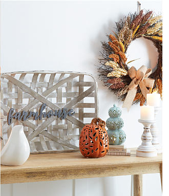 An assortment of fall themed décor on a wooden end table. Shop fall décor.