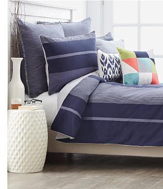 A bed made with a blue & light blue print comforter & matching pillows. Shop bedding.