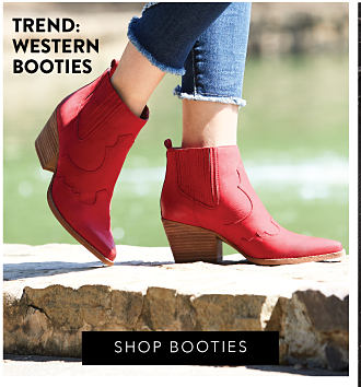 A woman wearing blue jeans & red western booties. Shop booties.