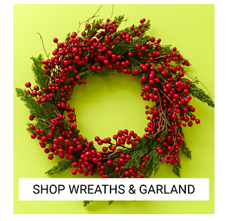 A green Christmas wreath with red berries. Shop wreaths & garlands.