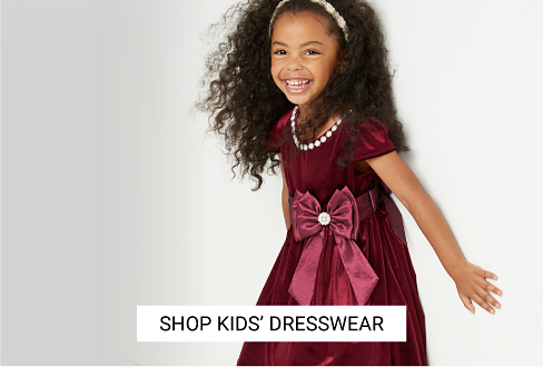 A girl wearing a burgundy velvet short sleeved dress. Shop kids dresswear.
