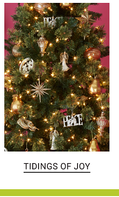 A Christmas tree decorated with joyful ornaments. Shop Tidings of Joy.