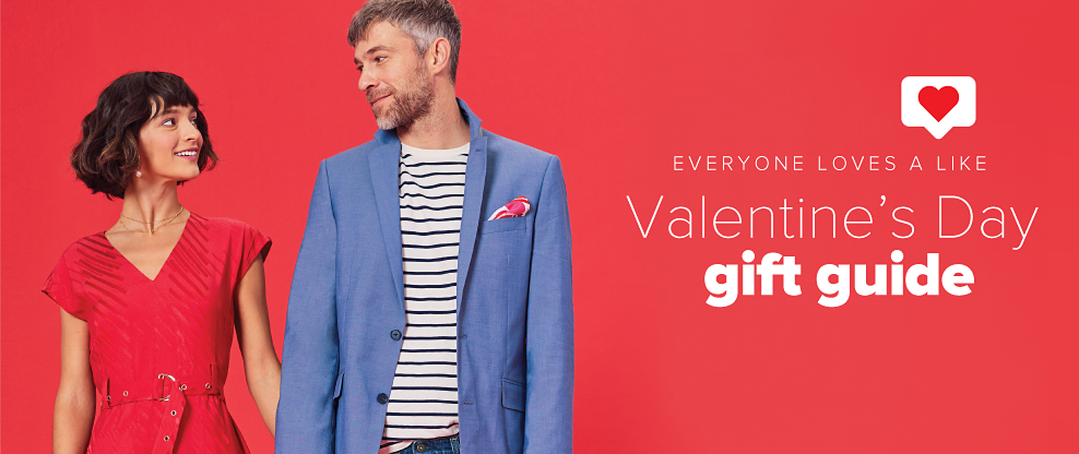 A woman in a red dress holding hands with a man in a white and navy stripe shirt, blue blazer and jeans. Everyone loves a like. Valentine's Day gift guide