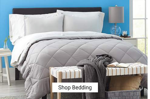 A bedroom featuring a blue wall and a queen bed dressed in a gray, diamond-pattern comforter. A bedroom bench sits at the foot of the bed. Shop bedding.