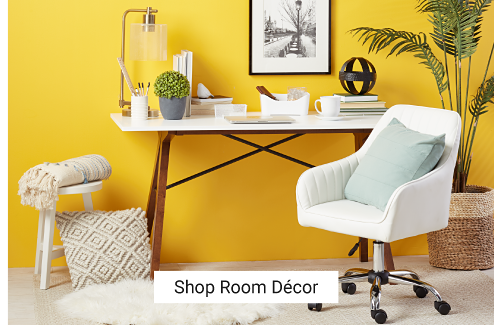A home office featuring a yellow wall, a white desk featuring dark wood legs, a white rolling desk chair and a potted palm tree. Shop Room Decor.