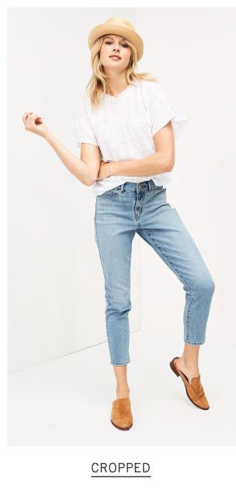 92b33a8f39b A woman wearing a straw porkpie hat, white tee, cropped blue jeans & brown