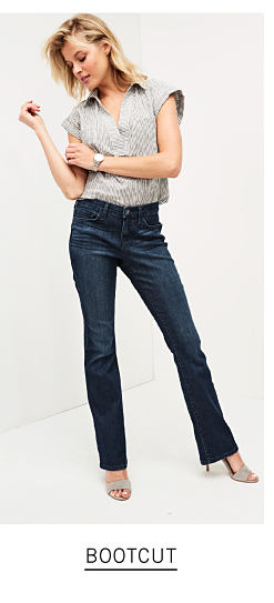 6fad2cbe A woman wearing a gray short sleeved button front blouse, boot cut blue  jeans &