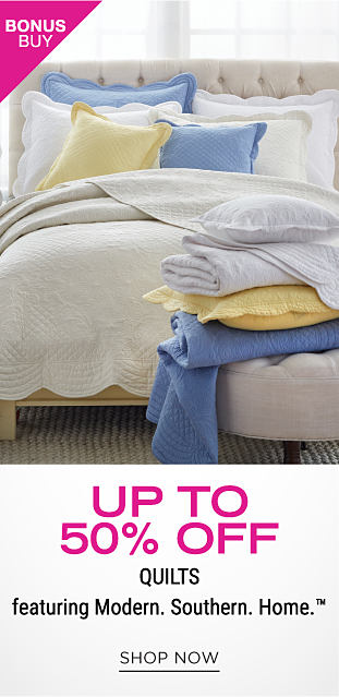 A bed with a white quilt and a stack of pillows and folded comforters in white, yellow and blue sitting in front of the bed. Bonus buy. Up to 50% off quilts featuring Modern. Southern. Home. Shop now.