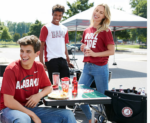 A young man wearing a reed, black & white Alabma T shirt & blue jeans sitting at a picnic table next to a young man wearing a red, white & gray Bama T shirt & black jeans & a young woman wearing a red & white Roll Tide T shirt & blue jeans.