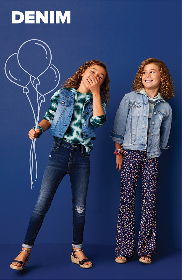 A girl in a green and white tie dye hoodie, with a denim vest over it and blue jeans. She holds an illustration of balloons. Another girls stands beside her, and she wears a green, blue and white hoodie with a denim jacket over it and loose floral pants. Denim.
