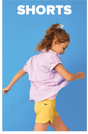 A girl in a pink button up shirt with the sleeves rolled up and yellow shorts. Shorts.
