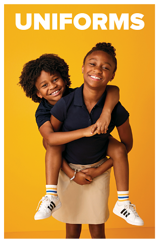 A girl in a blue polo and khaki shorts carries a boy, also wearing a blue polo, on her back. Uniforms.