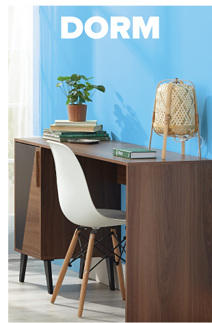A brown desk topped with a lamp, plant and stack of books. Dorm.