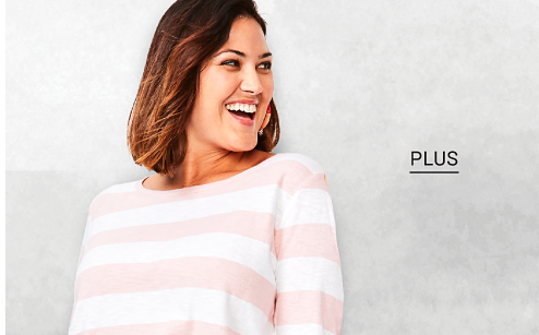 A woman in a pink and white sweater. Shop plus.
