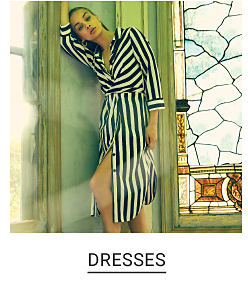A woman wearing a black & white striped long sleeved dress. Shop dresses.