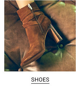 A woman wearing brown suede booties. Shop shoes.