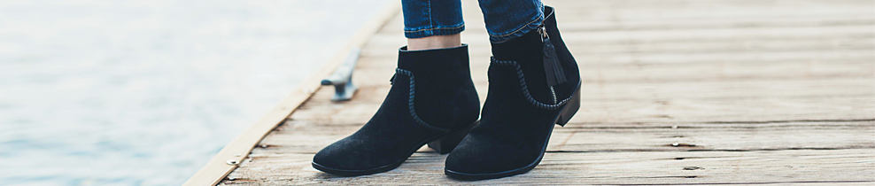 A woman wearing a pair of black suede sbooties. Women's boots. Check out the season's hottest styles & fall for your new favorite pair. Shop booties.