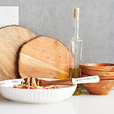 A wooden cutting board, a wooden bowl & a wire basket.