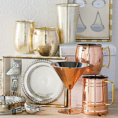 An assortment of hammered copper mugs, silver wine bottle stoppers & other barware essentials.