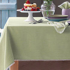A wooden dining table with a multi-colored print linen table runner.
