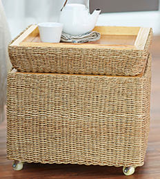 A wicker & wood wheeled end table with a flip-up serve tray top.