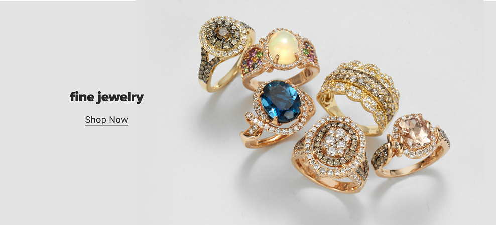An assortment of gold rings. A halo ring features white diamonds and brown diamonds with more gemstones along the sides. A gold ring features an opal and a white diamond halo with gemstones along the sides. A gold ring features a blue topaz and white diamonds. A multi-band ring features rows of white diamonds and scalloped edges. A large white and brown diamond ring. A gold ring features a pink morganite with white and brown diamonds. Fine jewelry. Shop now.
