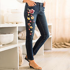 A woman wearing blue jeans with floral embroidery detail. Shop jeans.