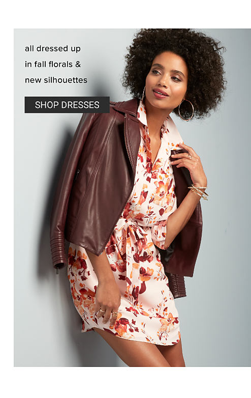 A woman wearing a brown leather jacket over a multi colored floral print dress. All dressed up in fall florals & new silhouettes. Shop dresses.