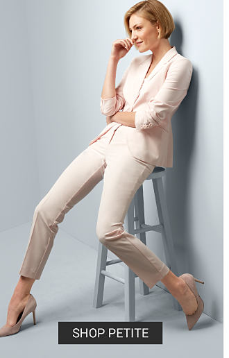 A woman wearing a white pant suit, white top & white heels. Shop petite.