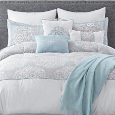 A bed with a white comforter and pillows to match. Shop bed in a bag.