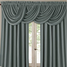 A window with draped curtains. Shop window treatments.