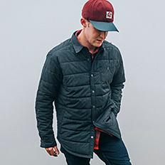 A man wearing a burgundy baseball cap, a navy puffer jacket, blue jeans & black sneakers. Shop men.