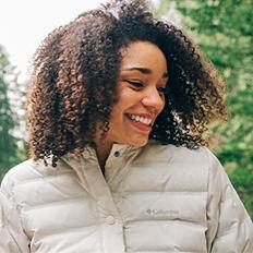 A woman wearing a white puffer jacket. Shop women.
