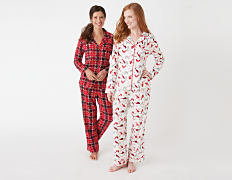 A woman wearing red & black plaid flannel pajamas standing next to a woman wearing white pajamas with a multi colored dot patterned print. Shop pajama sets.