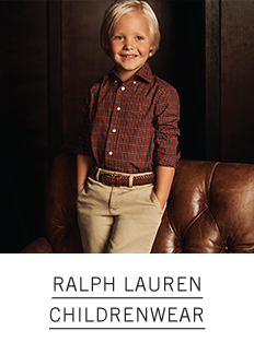 A little boy in a red plaid dress shirt with a brown belt and khakis. Ralph Lauren Childrenwear.