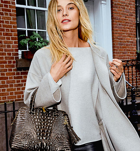 A woman carrying a brown croco leather handbag. Browse our new fall catalog. View now.