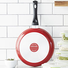 A red & silver skillet with a black handle. Shop cookware.