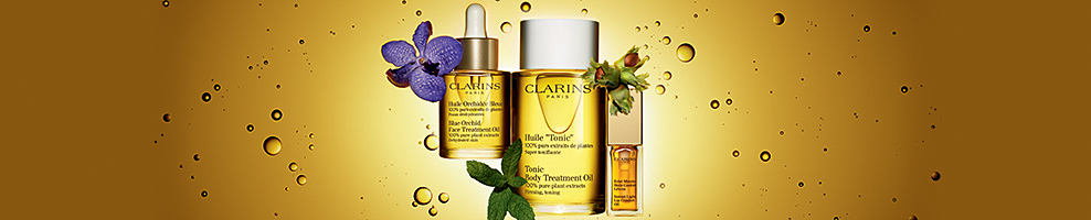 3 bottles of Clarins beauty products on a gold background. Clarins. Beauty made in France since 1954. Inspired by nature. Powered by plants. offering skin care & make up innovations for every moment of your life.