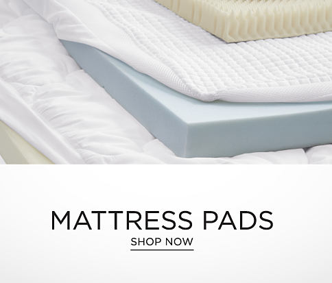 A stack of mattress pads in a variety of styles and thickness. A white fitted sheet is pulled back to reveal one of the pads. Mattress pads. Shop now.