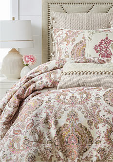 A bed made with a multi-colored paisley patterned comforter, matching pillows & other styles of throw pillows. Designer bedding. Shop now.